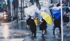台風のときの強風と大雨にさらされる人たちの写真